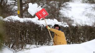 Man shovels snow off road in Sutton, Cheshire