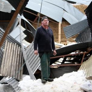 Sheep farmer James McHenry with his lambing shed, which collapsed with the weight of snow over the weekend, killing sheep and lambs at his farm in the Glens of Antrim, Northern Ireland