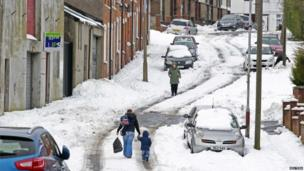 People walk through heavy snow as wintry weather continues to cause havoc across the United Kingdom, in north Belfast, on 25 March 2013