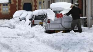 A man uses a shovel to clear snow from his car in Llangollen, north Wales, on 25 March 2013