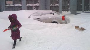 A girl with a plastic spade walks past a buried car