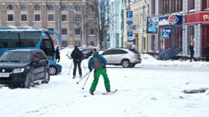 Skiers move around stranded vehicles