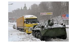 An armoured personnel carrier tows a vehicle on a Kiev road