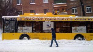 A man walks past a trolleybus