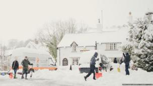 People clearing snow in Llanferres near Mold in Flintshire on Saturday