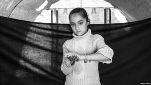 May, eight, holding up her bracelets