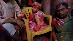A young Hindu devotee sits covered in coloured dye at the Banke Bihari temple, dedicated to Lord Krishna, during Holi festival celebrations in Vrindavan, India