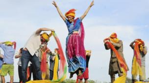 A tourist celebrates after finishing first in a turban tying competition held as part of the celebrations of Holi, also known as the Festival of Colours, in Jaipur,