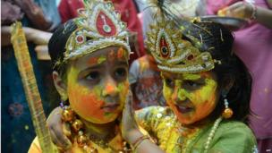 Indian children dressed as Lord Krishna (L) and Radha play with coloured powder during a Holi celebration at a temple in Amritsar on 26 March 2013.