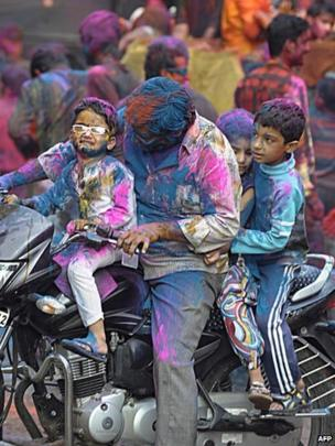 An Indian man drives a motor-bike with three children during Holi celebrations in Hyderabad on 26 March 2013.