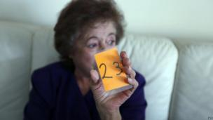 Pensioner Anna Ksiourou, 65, holds up her number as she waits for food aid and basic supplies at the Red Cross in Nicosia, Cyprus, 27 March