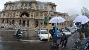 A journalist works in front of the building of Italy's Court of Cassation in Rome, 26 March