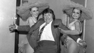 Two women catching Norman Collier as he falls backwards