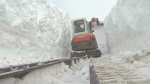Digger clearing track of snow on Snowdon Mountain Railway in March, 2013