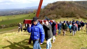 People walking up a hill carrying a cross. Photo: John Wilkes