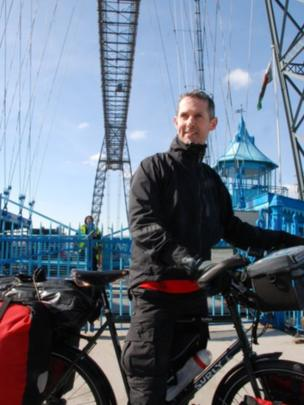 Rob Graham, who is beginning a 12,000 mile bicycle ride to New Zealand, at the Newport Transporter Bridge