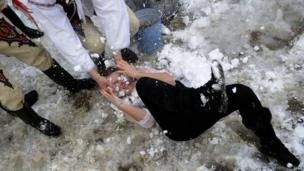Young Slovak men dressed in traditional costumes rub snow into the face of a woman (1 April 2013)