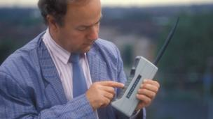 Man from 1980s using a mobile phone of the time