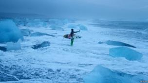 A surfer on a beach surrounded by icebergs