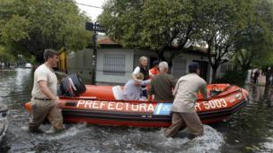 Members of the Argentine Coast Guard rescue an old woman from her home in La Plata, 3 April 2013
