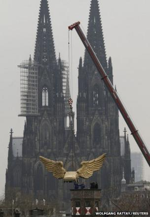 The Fluegelauto (winged car) by German artist HA Schult is lowered to the top of Cologne's armoury