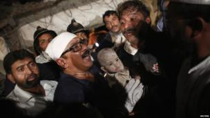 Rescuers carry a child from the rubble in Thane, Mumbai, on 4 April 2013