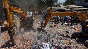 Excavators clear debris in Thane, Mumbai, on 5 April 2013