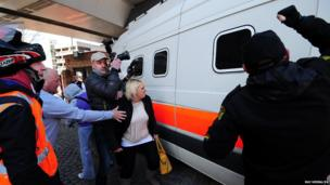 An onlooker reacts to a police van believed to be transporting Mick or Mairead Philpott as it leaves Nottingham Crown Court