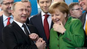 Russian President Vladimir Putin holds the hand of German Chancellor Angela Merkel as they visit the Russian booth during a tour through the Hanover Messe on the first day of the industrial trade fair