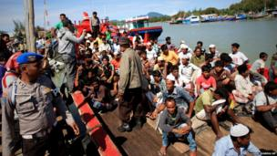 Rohingya migrants sit on the boat at a port in Aceh