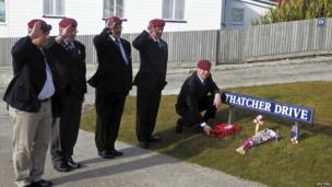 A group of former British paratroopers, who fought in the Falklands War, salute as they leave a wreath for former British prime minister Margaret Thatcher at a street sign in her name.