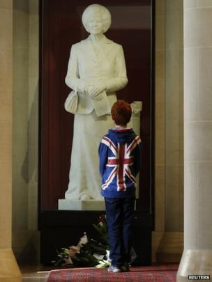 A boy stands in front of a statue of former British prime minister Margaret Thatcher, on display in the Guildhall Art Gallery in the city of London. Date: 8 April 2013. In 2002 a man decapitated the statute on display but it was later restored