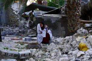 An Iranian woman sits among the rubble of buildings after an earthquake struck southern Iran