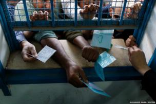 Palestinians present their ration cards as they wait to receive food supplies inside a United Nations food distribution centre in Gaza City