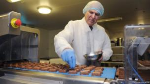 Business Secretary Vince Cable decorates chocolate bars during a visit to Casemir Chocolate in Enfield