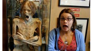 Rhona Gough imitates a mummy in a museum