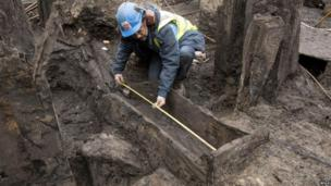 Man measuring a wooden drain buried deep in the mud