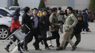 Journalists question a worker near the border between North and South Korea, 11 April 2013