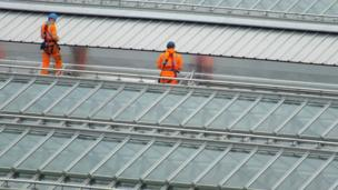 Workmen on a railway station roof