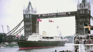 The Royal Yacht Britannia passing under Tower Bridge, London
