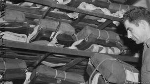 Tech Sgt Francis Scott Kee packs away parachutes at Duxford