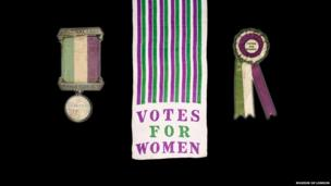 Suffragette prisoner's silver hunger strike commemorative medal, Suffragette motor scarf of white Japanese silk with green and purple stripes and a Suffragette rosette and badge with ribbons