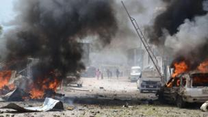 Cars burn outside the main court buildings in Mogadishu, after an attack by al-Shabab