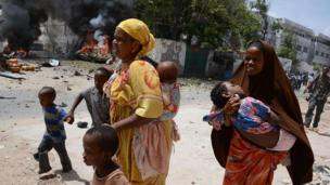 Two mothers run with their children in Mogadishu