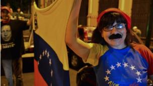 Supporter of Nicolas Maduro, with a fake moustache, celebrates his win in the presidential election