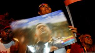 A supporter of Venezuelan presidential candidate Nicolas Maduro holds a poster with an image of late President Hugo Chavez as she celebrates after the official results gave Maduro a victory
