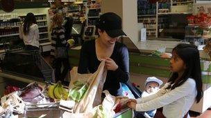 Nayeli Gonzalez packs her groceries with her children