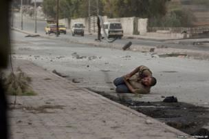 A wounded Syrian civilian lies in the street as he tries to escape the line of fire after being targeted by a Syrian army sniper in Aleppo, 20 October 2012