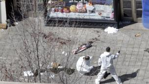 Two men in hazmat suits investigate the scene of the first bombing on Boylston Street in Boston 16 April 2013