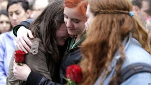 Emma MacDonald, 21, left, is comforted by Rachael Semplice, 22, center, as Juliana Hudson, 23, looks during a vigil for the victims of the Boston Marathon explosions at Boston Common, Tuesday, April 16, 2013.